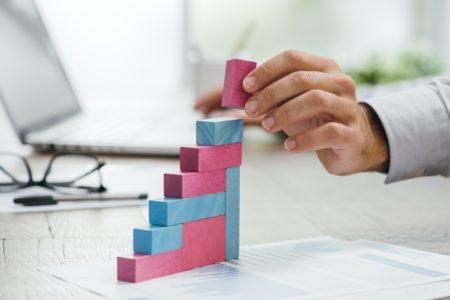 Businessman building a growing financial graph